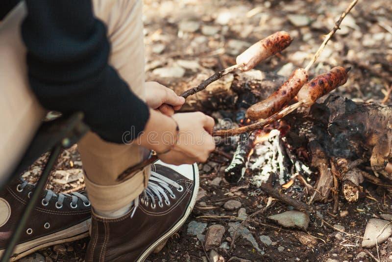 Camper dans le sauvage - saucisses grillées au-dessus du feu de camp photos libres de droits