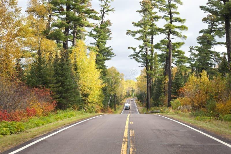 Camper en pick-up vrachtwagen rijdt onder de hoge pijnen en herfstkleur op de Gunflint Trail van Minnesota stock afbeeldingen