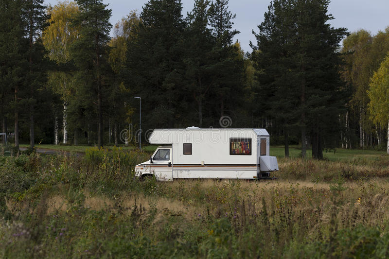 Camper in the field. A parked camper on a field with some trees in the background stock photo