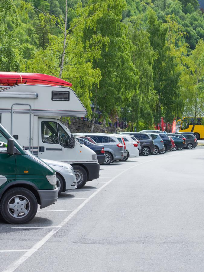 Camper home and cars on rest stop area. Camper motor home with canoe on top roof and cars on rest stop location, parking area. Travel, active lifestyle concept royalty free stock image