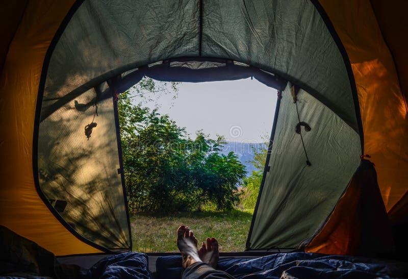 camper Matin dans la tente Jambes femelles dans une tente verte images stock