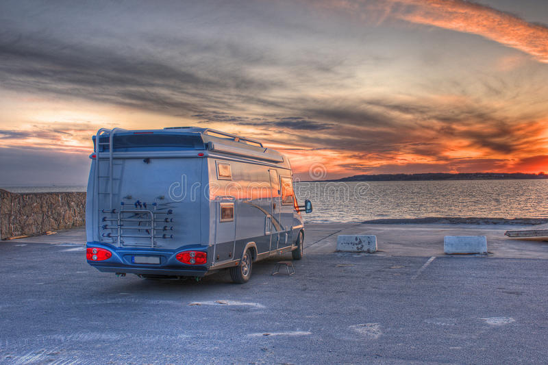 Camper parked on the beach in HDR. Dramatic sunset with caravan at a beach parking in HDR stock photo