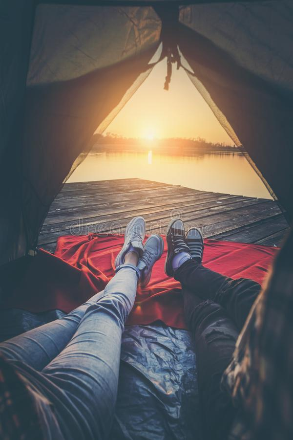Campers enjoying sunset. Young couple in love camping on lake docks, lying in the tent, enjoying beautiful sunset over the lake royalty free stock photo