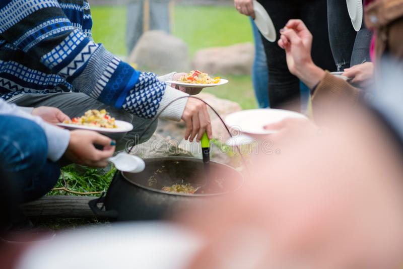 Campers sharing food cooked on sooty pot on campfire. People at survival camp.  royalty free stock image