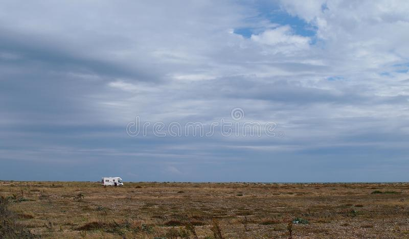 Campervan on the headland of Dungeness in Southern England. Dungeness is one of the biggest shingle beaches in Europe and has attracted many artists over the royalty free stock photos