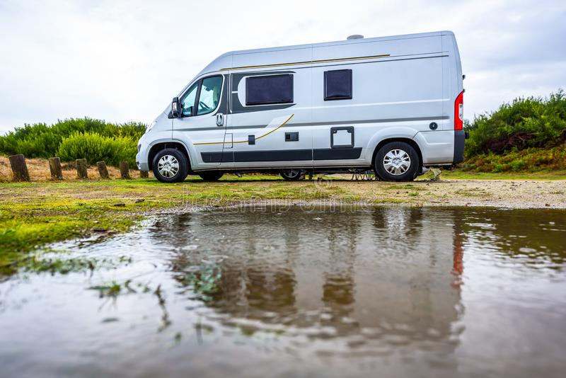Campervan or motorhome camping on rainy day with rain puddles. Family vacation road trip with camper van, motor home or RV in with bad weather. Holiday royalty free stock image