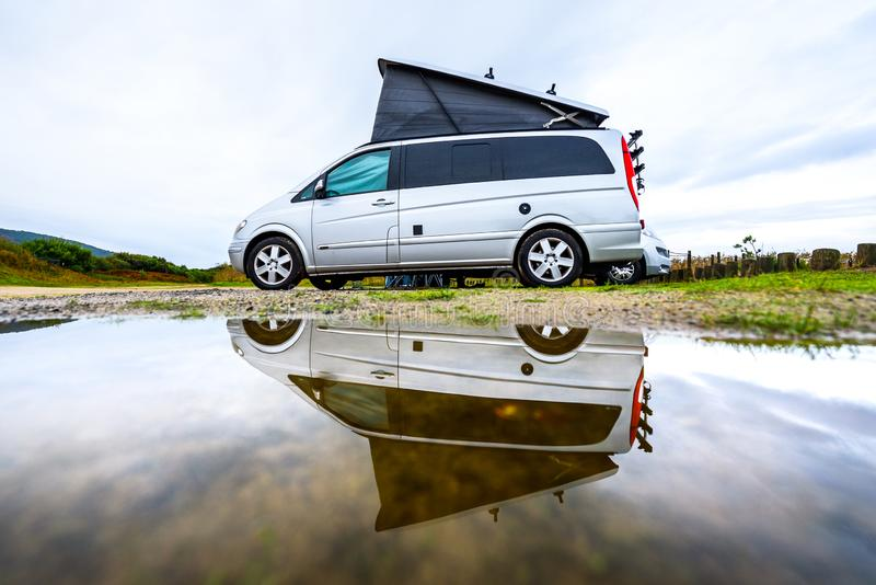 Campervan or motorhome camping on rainy day with rain puddles. Family vacation road trip with camper van, motor home or RV in with bad weather. Holiday royalty free stock photo