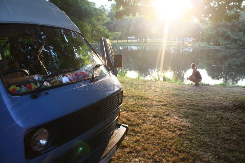 Campervan och flicka vid sjön royaltyfri fotografi