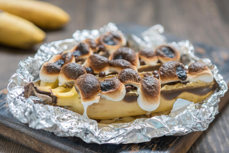 Campfire banana with marshmallow and chocolate chips stock photo
