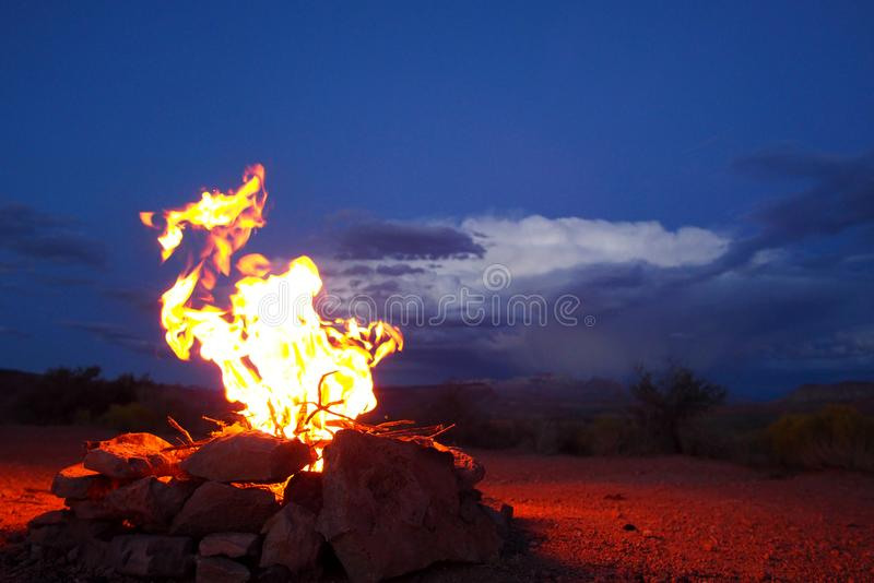 Campfire in front of desert storm. A campfire begins to roar out in the desert as an evening storm begins to roll in through the background stock images