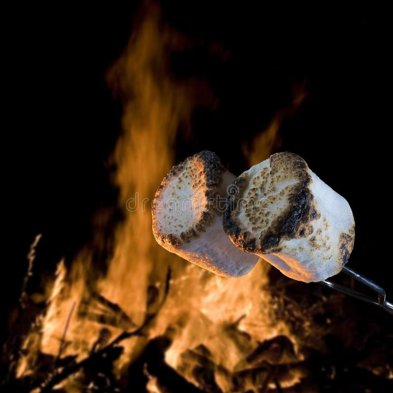 Campfire and browned marshmallows. Two marshmallows being roasted over a campfire to make smores royalty free stock images