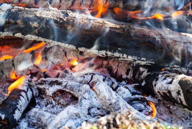 Campfire with burning firewood, close up. Glowing embers smoldering in the fireplace royalty free stock photos