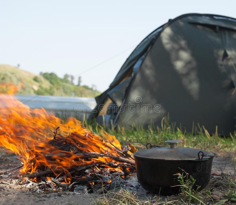 Campfire, cauldron and tent near the river stock photography