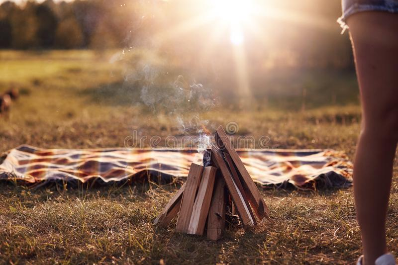 Campfire on green grass, plaid lies near, beautiful nature, calm atmosphere, sunshine, no people on photo. Summer vacation, picnic. Lifestyle, leisure and royalty free stock images