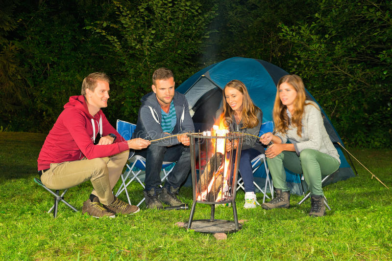 Campfire. A group of friends sitting around a campfire in front of a tent stock image