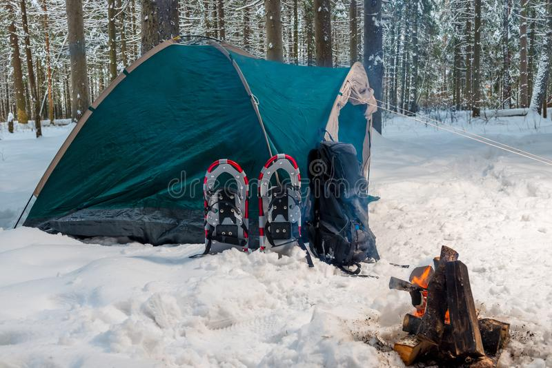 A campfire near a tent in a winter camping royalty free stock images