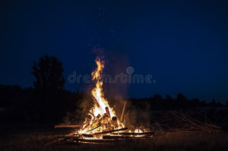 Campfire at night, with its soothing flickering flames and red and orange glow of the burning logs at dark night. Burning logs in orange flames. Background of royalty free stock photos