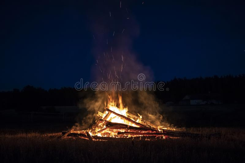 Campfire at night, with its soothing flickering flames and red and orange glow of the burning logs at dark night. Burning logs in orange flames. Background of stock photos