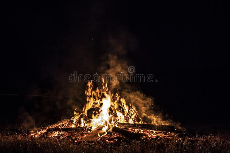 Campfire at night, with its soothing flickering flames and red and orange glow of the burning logs at dark night. Burning logs in orange flames closeup stock photo