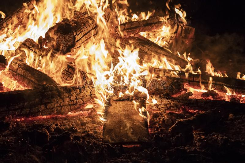 Campfire at night, with its soothing flickering flames and red and orange glow of the burning logs at dark night. Burning logs in orange flames closeup royalty free stock image