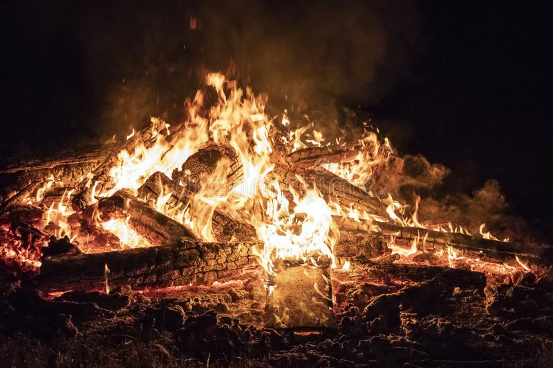 Campfire at night, with its soothing flickering flames and red and orange glow of the burning logs at dark night. Burning logs in orange flames closeup stock photos