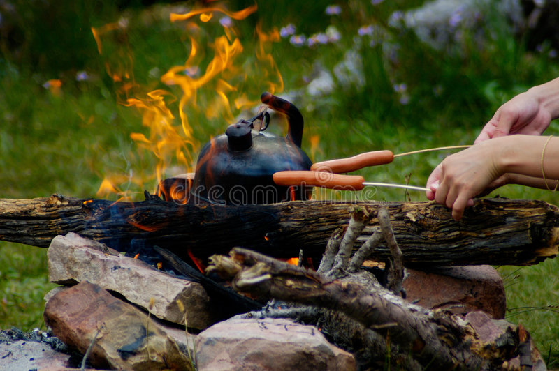 Campfire picnic. Teakettle and sausages stock photo