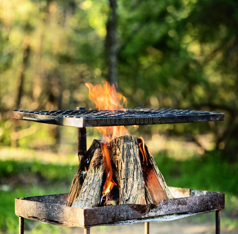 Campfire to make a braai or barbecue. Open wooden fire for braai or barbecue outdoors in Africa. Close-up view with grid stock images