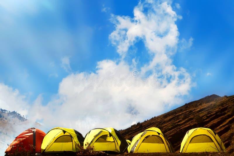 Campground στα βουνά Πολλές κίτρινες κόκκινες σκηνές adn ενάντια στο μπλε ουρανό με την κατάπληξη καλύπτουν στοκ φωτογραφίες με δικαίωμα ελεύθερης χρήσης