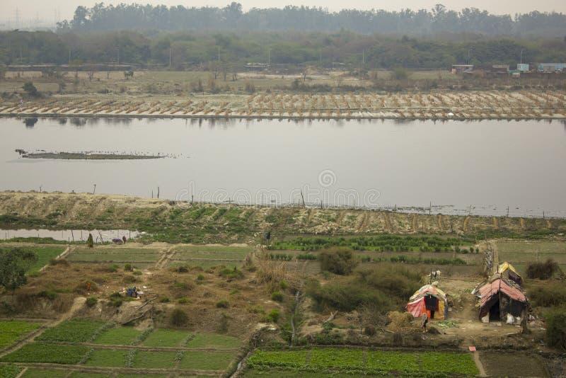 Campi verdi dell'azienda agricola sulle banche del fiume di Yamuna e delle case temporanee dei contadini Ponte della firma Delhi  immagini stock