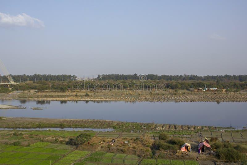 Campi verdi dell'azienda agricola vicino al fiume Yamuna ed alle case temporanee dei contadini Ponte della firma Delhi India immagine stock libera da diritti