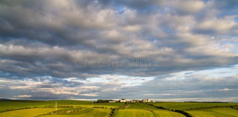 Campi verdi di rotolamento e un cielo drammatico in contea Antrim, Irlanda del Nord fotografia stock