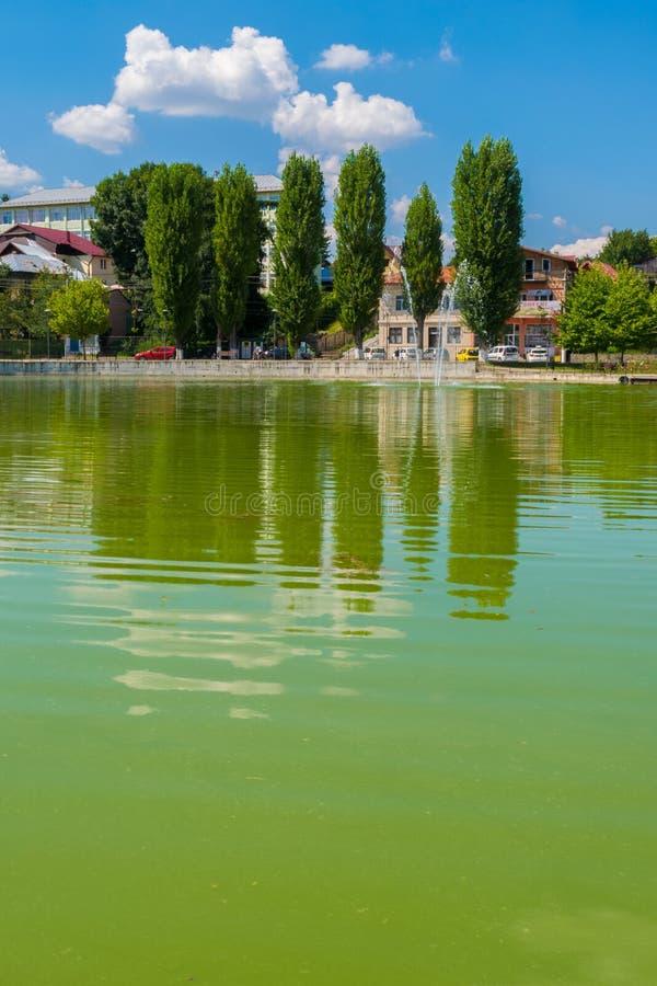 Campina, Румыния - 16-ое августа 2018: взгляд проклятого озера ` s невесты или озера церков показывая зеленые деревья и фонтан си стоковые фото