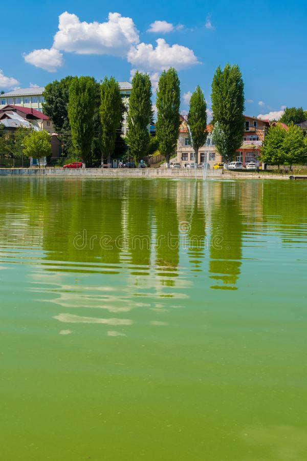 Campina, Romania - August 16, 2018: view of the cursed Bride`s Lake or the Church Lake showing green trees and water fountain sit. Uated in Campina, Prahova stock photos