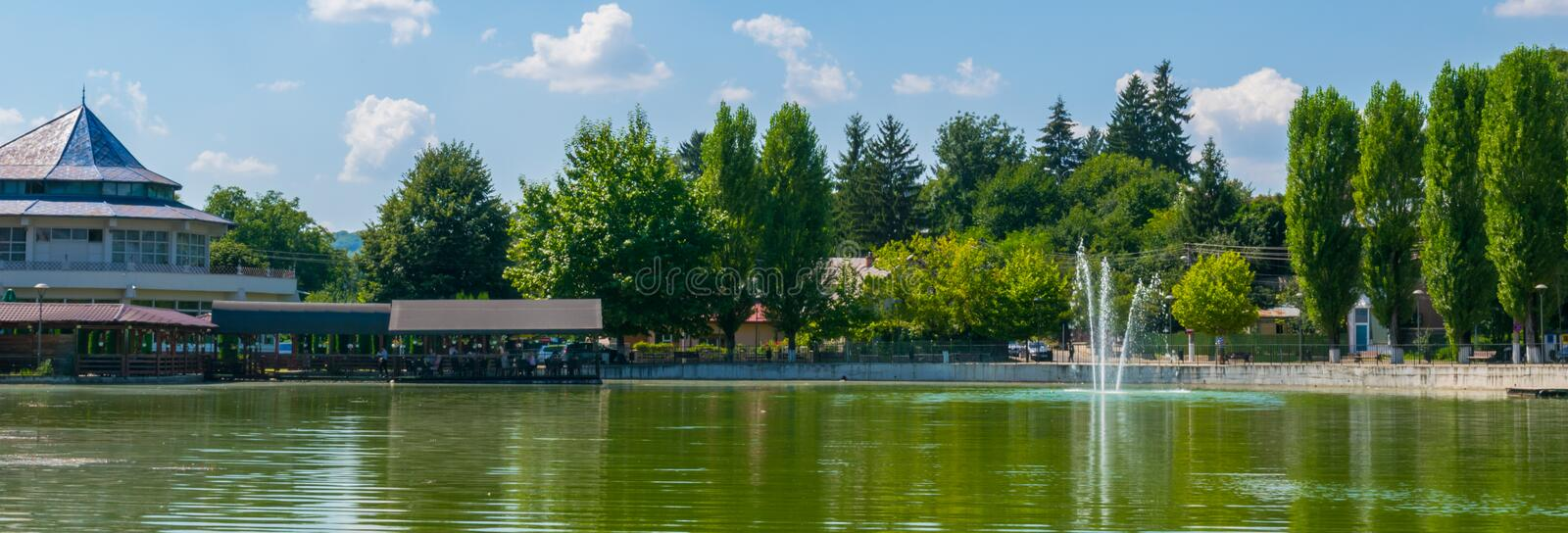 Campina, Romania - August 16, 2018: view of the cursed Bride`s Lake or the Church Lake showing green trees and water fountain sit. Uated in Campina, Prahova stock photo