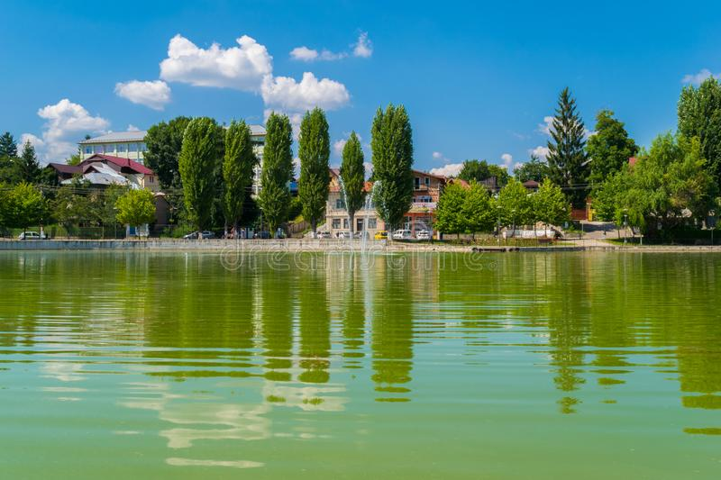 Campina, Romania - August 16, 2018: view of the cursed Bride`s Lake or the Church Lake showing green trees and water fountain sit. Uated in Campina, Prahova stock images