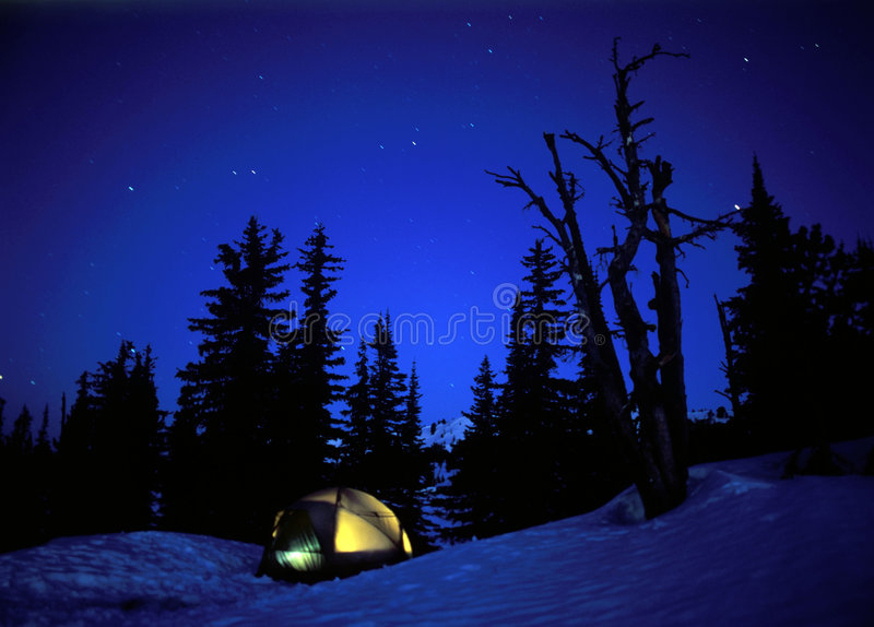 Camping. In a glowing tent under the stars in winter