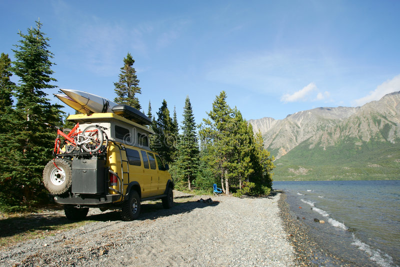 Camping. With yellow RV van at alpine lake, Alaska royalty free stock images