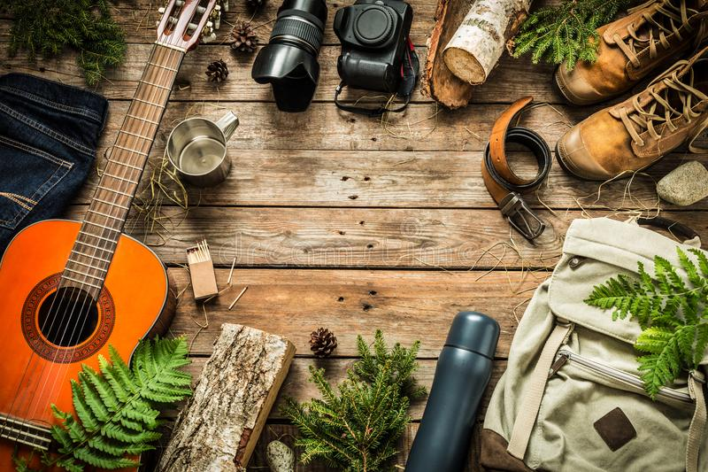 Camping or adventure trip scenery concept top view. Camping or adventure trip scenery concept. Backpack, guitar, boots, belt, thermos and camera on wooden royalty free stock image