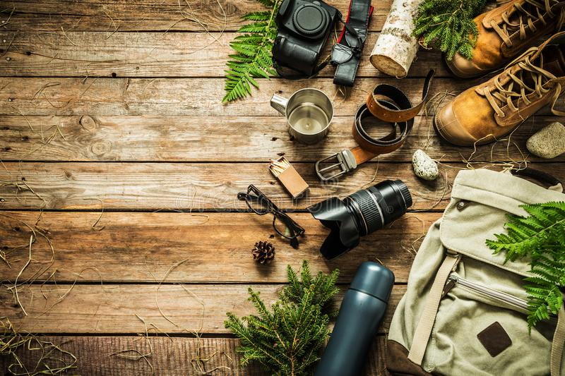 Camping or adventure trip scenery concept flat lay. Camping or adventure trip scenery concept. Backpack, boots, belt, thermos and camera on wooden background stock photos