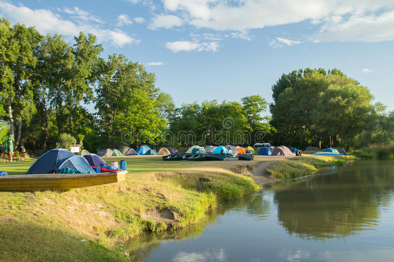 Camping area with tents near river stock image