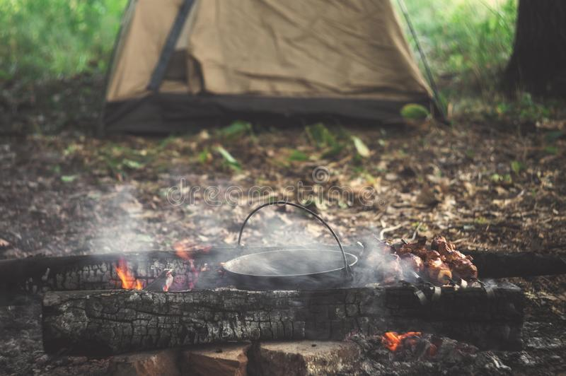 Camping. Bonfire and tent in the tourist camp. Relaxing on holiday in nature.  stock image