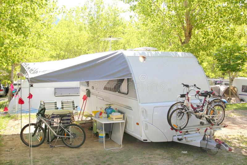 Camping camper caravan trees park bicycles. Camping camper caravan trees park with bicycles royalty free stock images