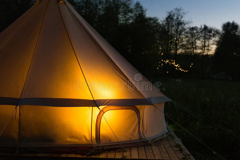 Camping canvas bell tent glows at night royalty free stock photo