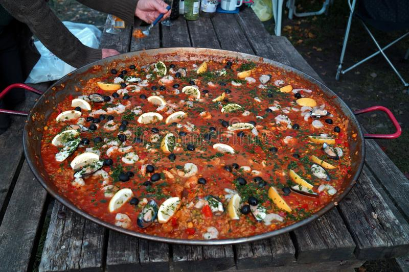 Camping cooking and making a traditional rustic spanish Paella on an open fire. Hand grabs a fork with a portion. stock photography