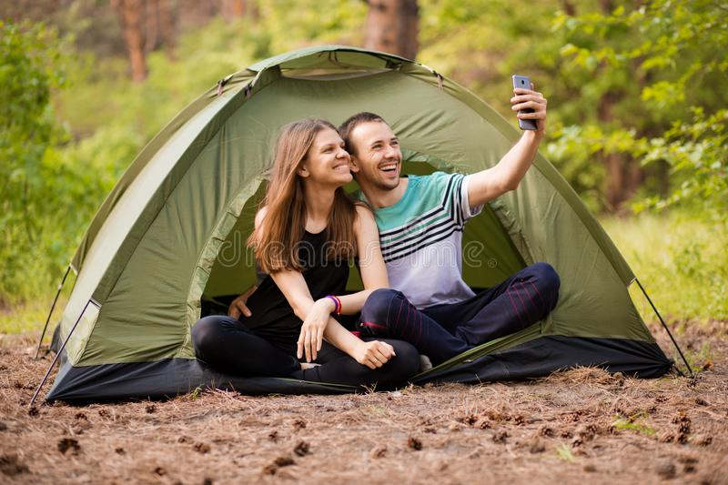 Camping couple in tent taking selfie. Happy friends having fun togheter. Concept lifestyle and technology royalty free stock photos