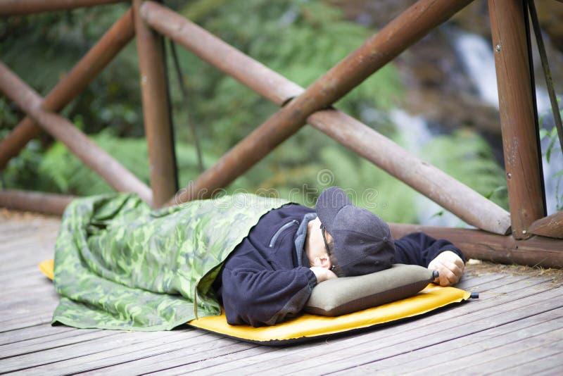 Camping d'amusement, homme heureux dormant dans la montagne images stock