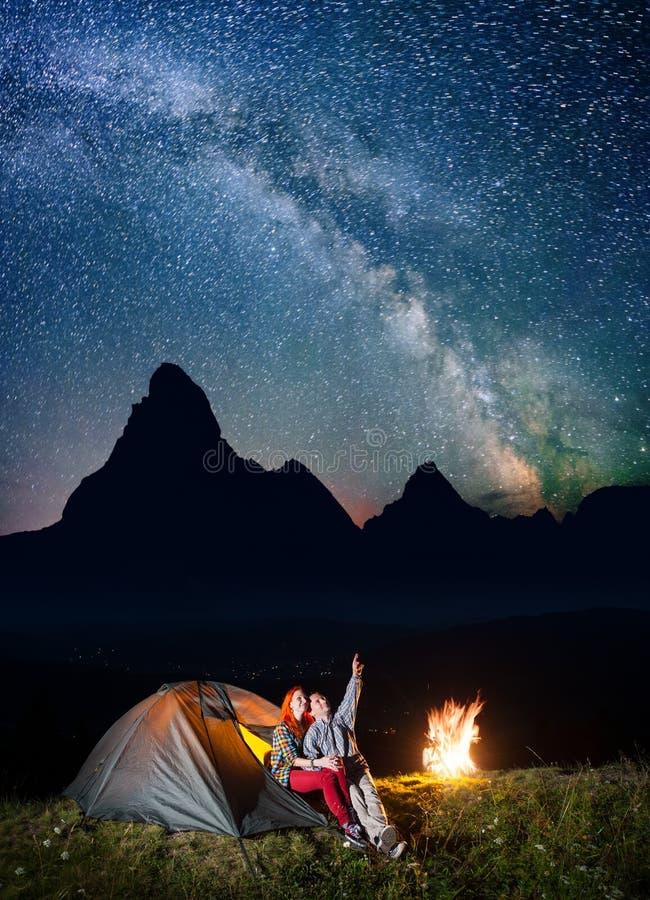 Camping de tente de nuit Randonneurs heureux de couples s'asseyant près de la tente et du feu de camp et appréciant le ciel étoil images stock