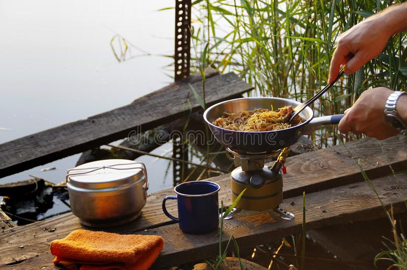 Camp cooking. Camping food making. Pasta on pan on tourist fire stove. Camp cooking on the shore of the lake stock photo
