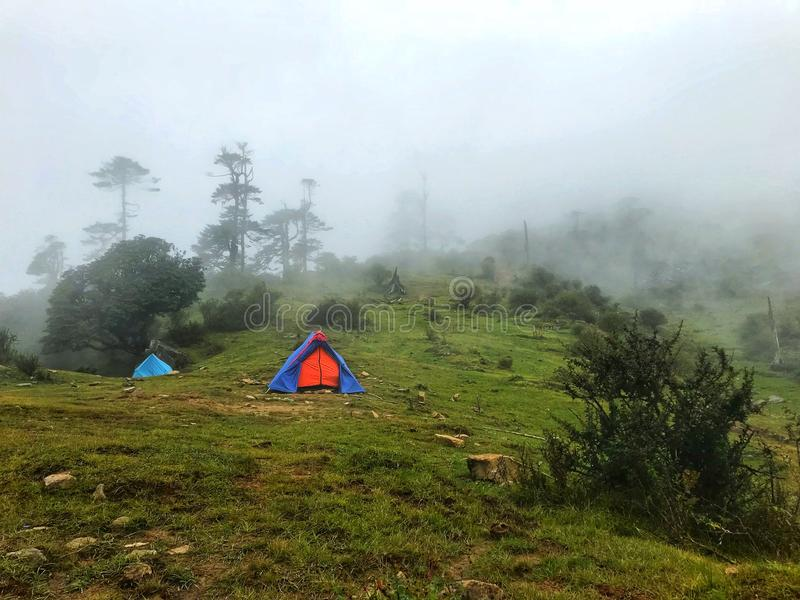 Camping in foot hills. Blue camping tent in the Himalayan hills with the clouds coming and going covering the top of the peak with beautiful green carpet on the stock photography