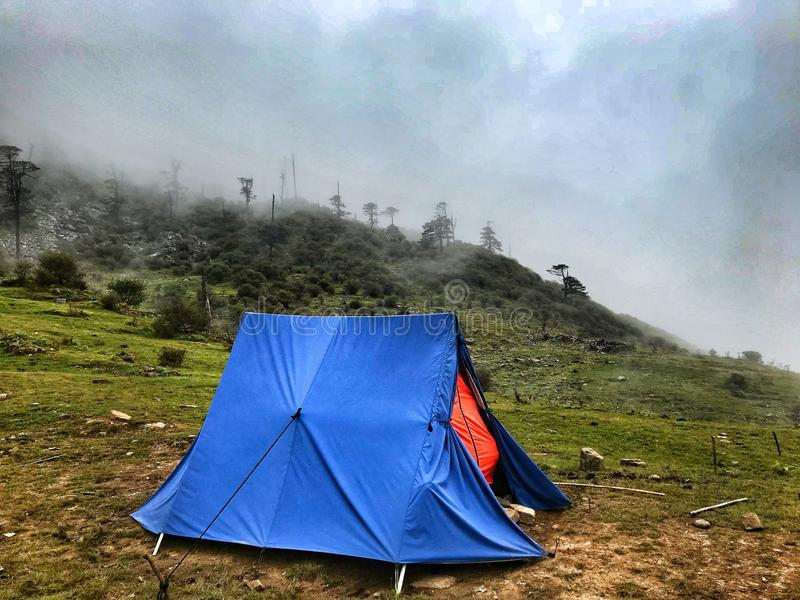 Camping in foot hills. Blue camping tent in the Himalayan hills with the clouds coming and going covering the top of the peak with beautiful green carpet on the royalty free stock photos
